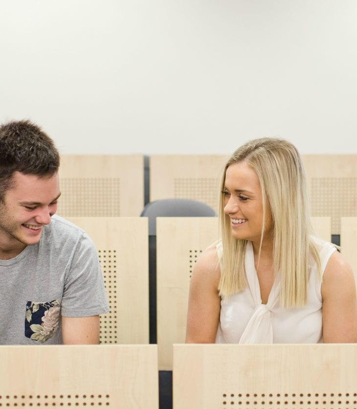 CSU students chatting in a lecture.