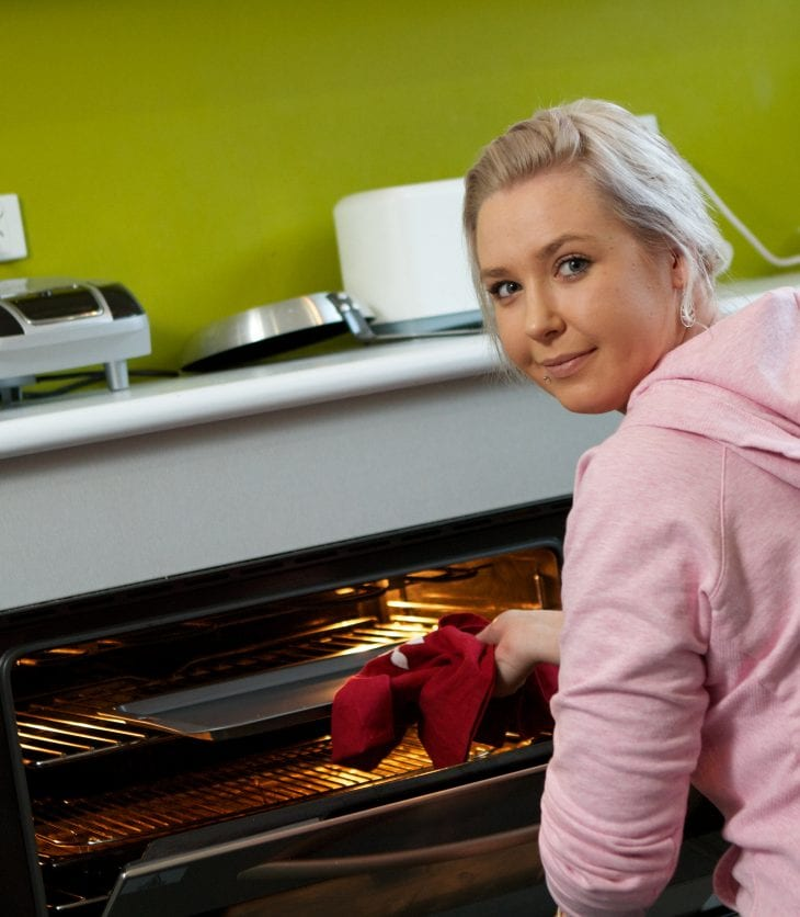 girl taking baked goods out of the oven