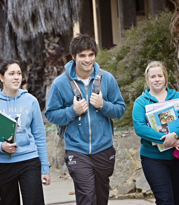 image of two female and a male student walking on campus