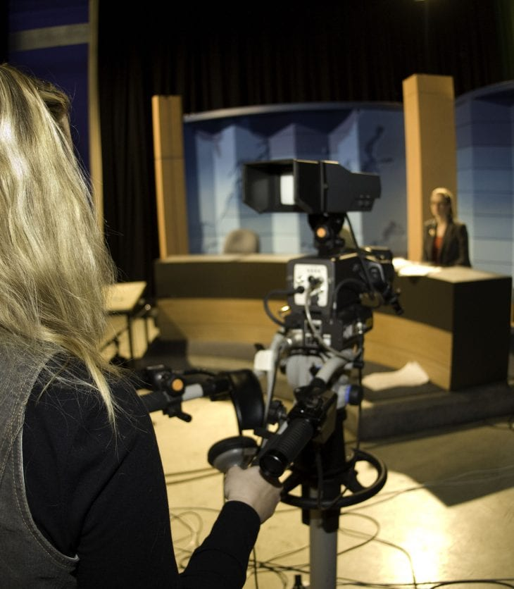 Student standing behind TV news camera