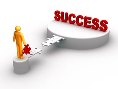 cartoon of a man holding a puzzle piece pacing the way to the word SUCCESS