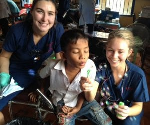 CSU students with a Cambodian child blowing bubbles