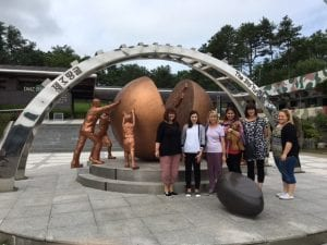 CSU social work students standing in front of historic sculpture in South Korea