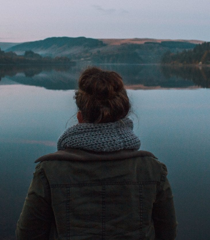 Young girl standing in front of lake