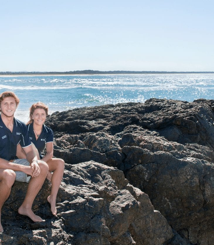 Two Port Mac students sitting on rocks at the Port Mac beach