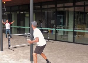 Two students playing tennis