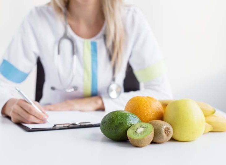 medical professional in background with assortment of fruits in the foreground