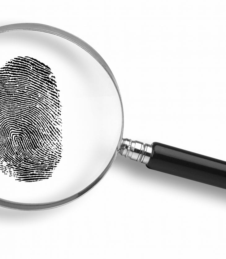 Magnifying glass and thumb print on white background.
