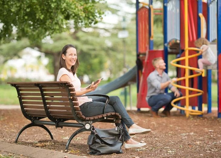 Woman sitting in playground with man and child playing in the background