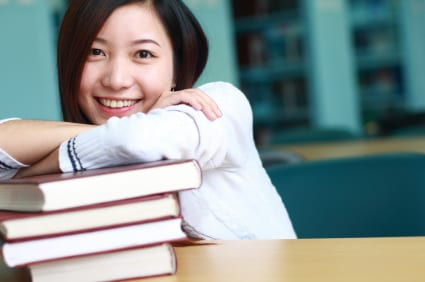 young female leaning on pile of books