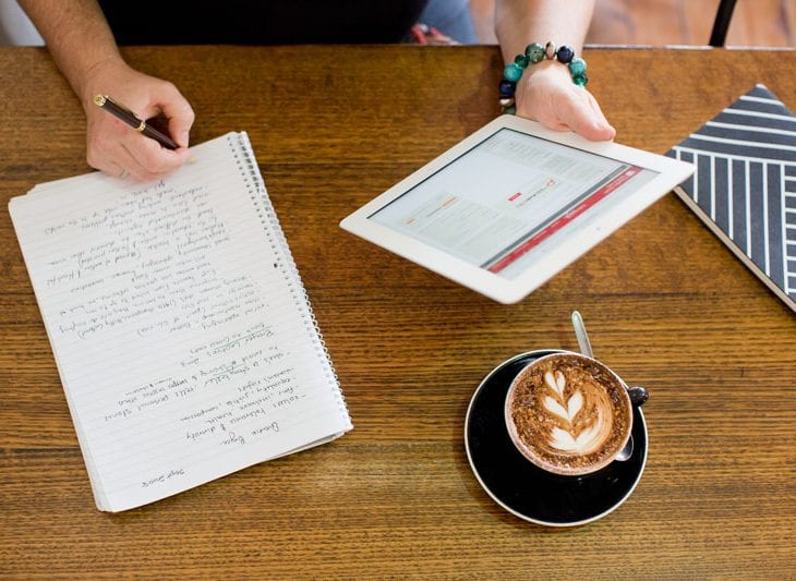 taking notes from iPad with coffee