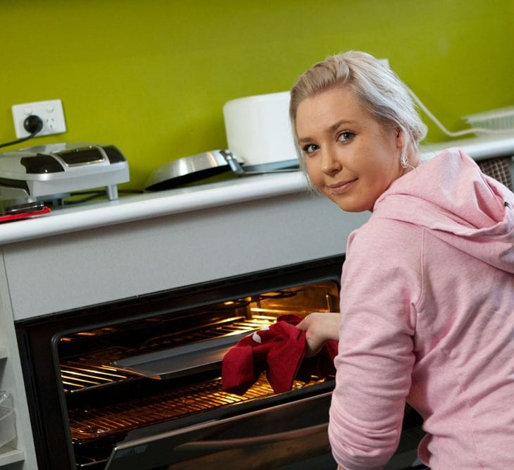 Student using the oven in shared dorm kitchen