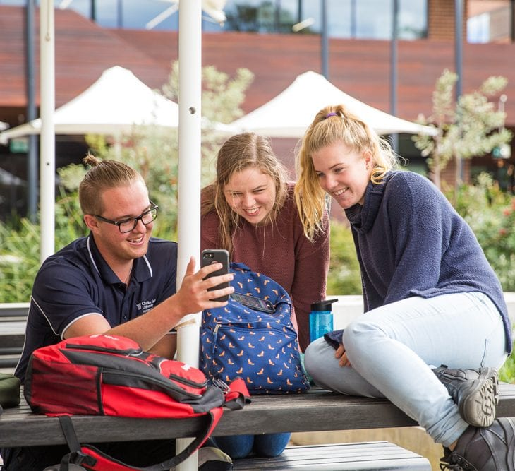 Group of students together looking at mobile phone