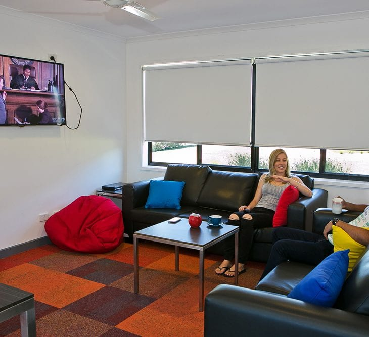 Two students watching TV in accommodation common area