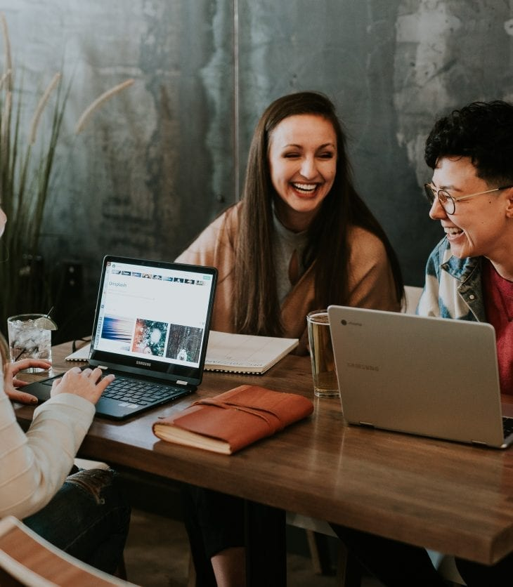a group of people meeting with laptops